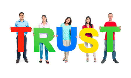 trust people: Multi-ethnic group of people holding TRUST letters