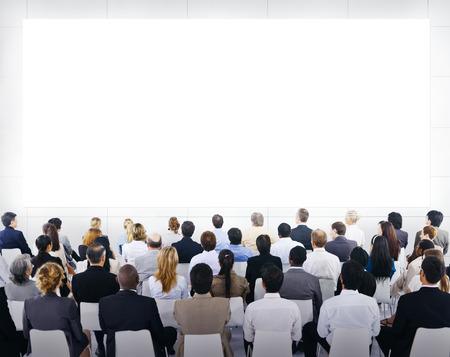 Group of business people sitting and looking at the blank presenation. Imagens