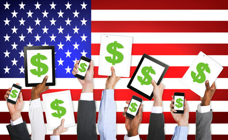 Multi-Ethnic Group Of Business People Holding Technology Devices With A Dollar Sign On A Screen And American Flag As A Background. photo