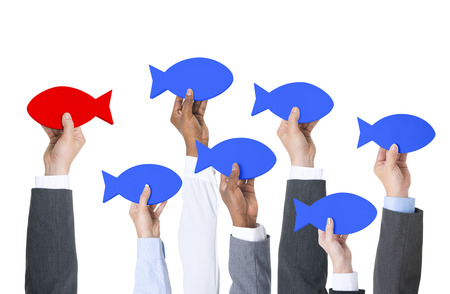 standing out in the crowd: Business people holding fish and thinking outside of the box.