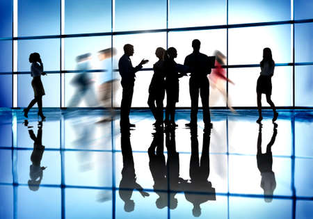 organized office: Silhouettes of Business People Working in an Office Building Stock Photo