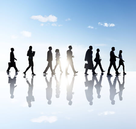 computers office: Side View Photo Of Silhouettes Of Business People Walking In Outdoors. Stock Photo