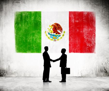 bandera mexicana: Dos hombres de negocios d�ndose la mano con la bandera mexicana Como Fondo