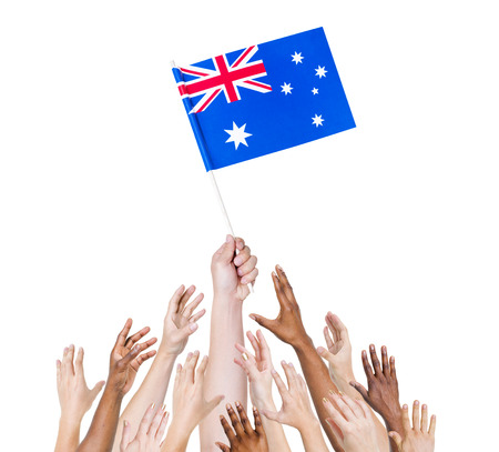 winning location: Human hand holding Australia flag among multi-ethnic group of peoples hand Stock Photo