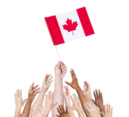 winning location: human hand holding Canada flag among multi-ethnic group of peoples hands Stock Photo