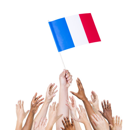 france  flag: Human hand holding France Flag among multi-ethnic group of peoples hand Stock Photo
