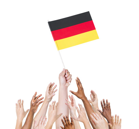 Human hand holding Germany flag among multi-ethnic group of peoples hand Stock Photo