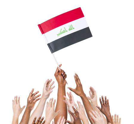 iraq flag: Human hand holding Iraq Flag among group of multi-ethnic hands Stock Photo