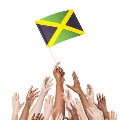 Group of multi-ethnic people reaching for and holding the flag of Jamaica.