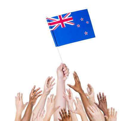 winning location: Human hand holding New Zealand Flag among group of multi-ethnic hands
