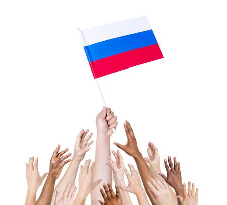 winning location: Human hand holding Russia Flag among group of multi-ethnic hands