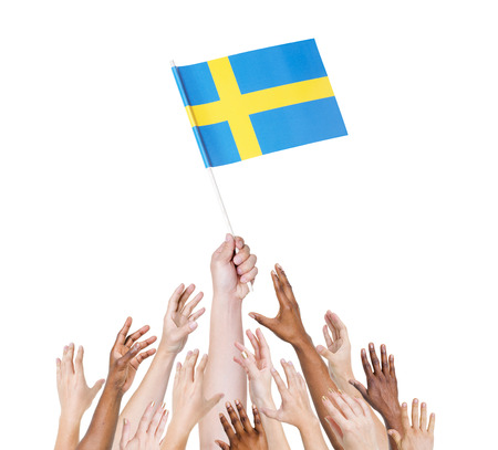Human hand holding Sweden flag among multi-ethnic group of peoples hand