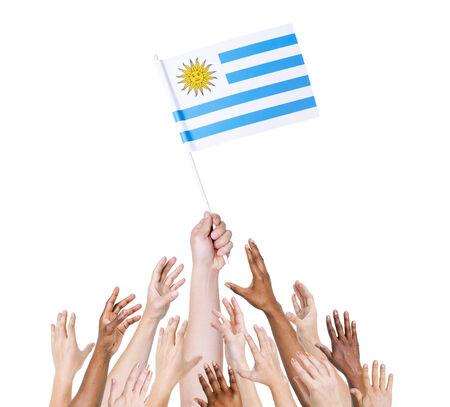 bandera de uruguay: La mano del hombre sostiene la bandera Uruguay entre grupo multi�tnico de las manos de la gente