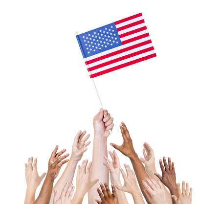 Group of multi-ethnic people reaching for and holding the flag of the United States of America. Reklamní fotografie