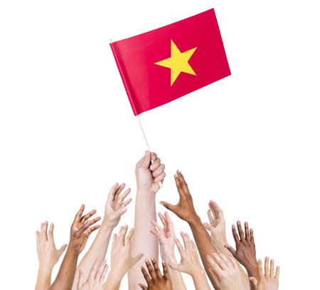 winning location: Human hand holding Vietnam flag among multi-ethnic group of peoples hand Stock Photo