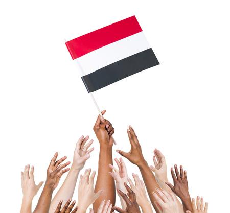 Human hand holding Yemen flag among multi-ethnic group of peoples hand
