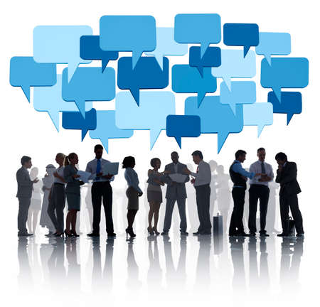 Group Of Business People Discussing And Blue Speech Bubbles Above Them. photo