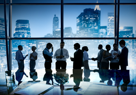 empleado de oficina: Grupo de hombres de negocios que discuten en vista de la ciudad se refleja en la mesa con el documento.