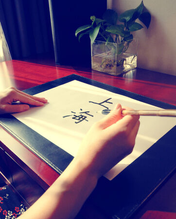 chinese calligraphy: Close up of a lady writing Shanghai in Chinese.