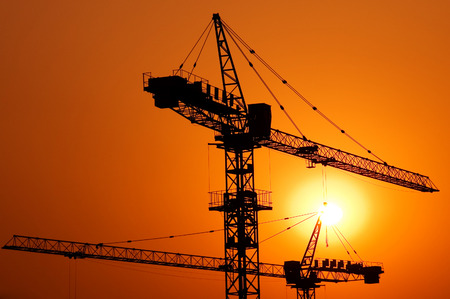 tower crane: Construction of a major housing project at sunset.