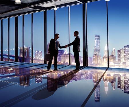 2 Multi-Ethnic Businessmen Shaking Hands Indoors With City As A Background