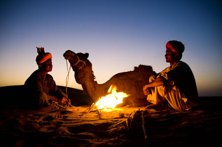 camel silhouette: Two indigenous Indian men resting by the bon fire with their camel.
