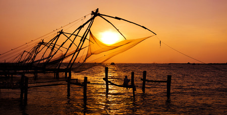 Indian man fishing under the great Chinese nets at Cochin, Kerela, India.  Imagens