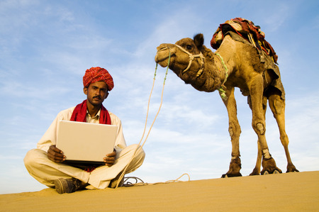 thar: Indigenous Indian man with his laptop out in a desert.
