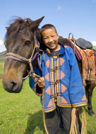 independent mongolia: Little boy tilting his head to his horse and smiling at outdoors.