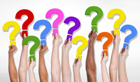 questions: Multi-Ethnic group of human hands holding question marks. Stock Photo