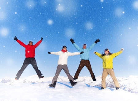 Group of young happy people jumping in snow and enjoying winter.  photo