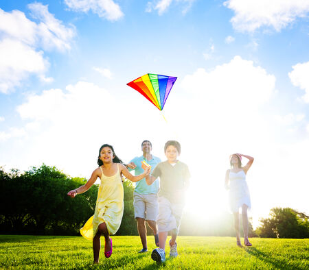 outdoor pursuit: Family playing kite outdoors.