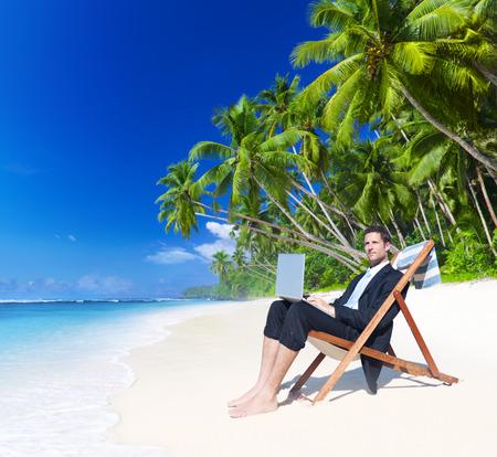 Businessman working with laptop on beach. Reklamní fotografie