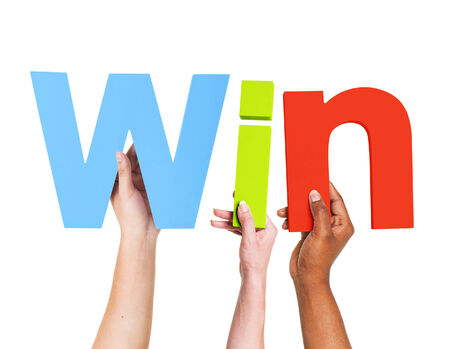 Multiethnic Arms Raised Holding Text Win photo