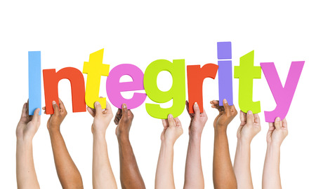 Multi-Ethnic Group Of People's Arms Raised Holding Letters That Form Integrity Stock Photo