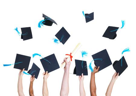 お祝いの印として卒業生の手を保持していると投げ卒業帽子のグループ 写真素材