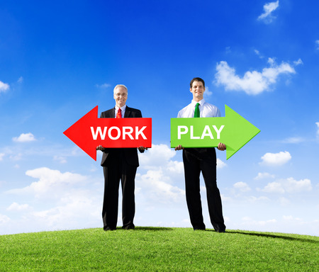 Two Businessmen Holding Contrasting Arrows for Work and Play photo