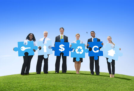 Group of Business People Holding Puzzle Pieces with Icons in an Open Field photo
