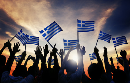 Silhouettes of People Holding the Flag of Greece photo