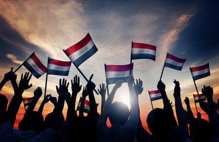 gente saludando: Siluetas de personas que ondeaban la bandera de Iraq Foto de archivo