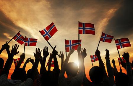 Groep Mensen Zwaaien Noorse Vlaggen in Tegenlicht