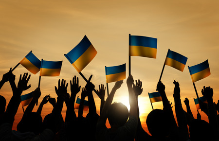 ukranian: Group of People Waving Ukranian Flags in Back Lit