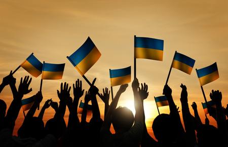 gente saludando: Grupo de personas que ondeaban banderas ucranianas en Contraluz Foto de archivo