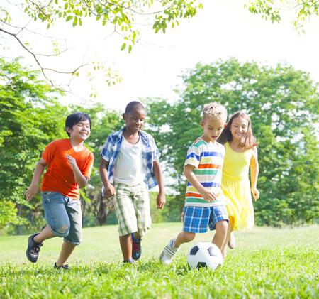 Niños que juegan a fútbol en el parque.