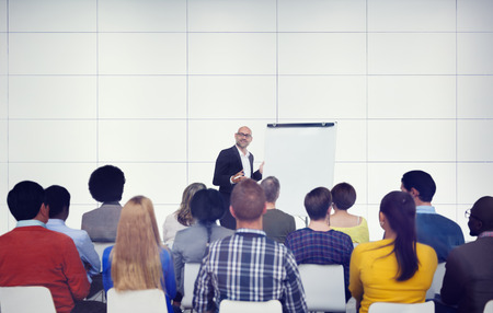presenting: Businessman Presenting in Front of Audience Stock Photo