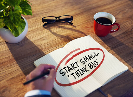 big break: Businessman Writing the Words Start Small Think Big