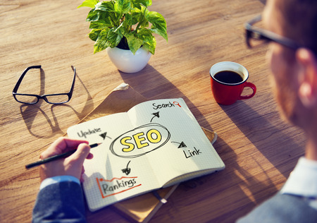 Hipster Writing SEO Concepts on his Note