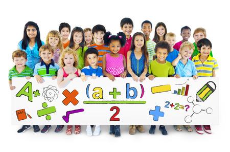 数学記号を保持している多様な元気な子ども 写真素材