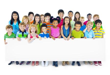 空の看板を保持している子供たちの多民族グループ