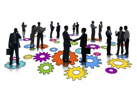 Silhouettes of group of busy business people standing on multi-colored gears. photo